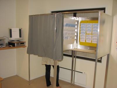 Norskt valbås med valsedlar bakom skynket. [«Stemmeavlukket» av Røed. Creative Commons Attribution-Share Alike 2.5.